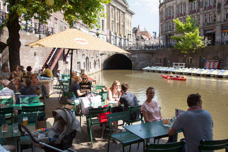 utrecht, netherlands, 15 may 2018: people sit and drink at outdoor restaurant at oudegracht in city center of medieval utrecht in holland