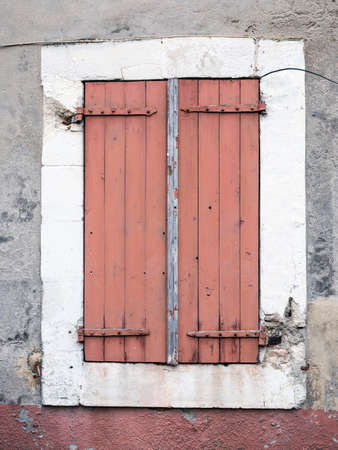 very old reddish brown painted shutters on window in medieval french house in provence luberon area
