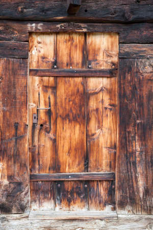 closeup of very old grungy brown wooden weathered planks of door in ancient swiss barn