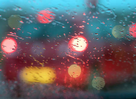 abstract pattern of colorful lights and rain drops during downpour on winshield of car after dark