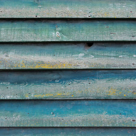 part of green wall on wooden barn or fence with horizontal planks