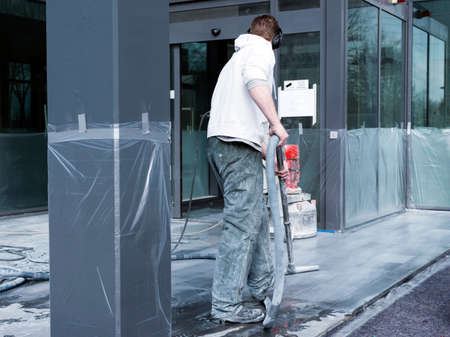 man cleans and polishes marble floor of office building with machine 版權商用圖片