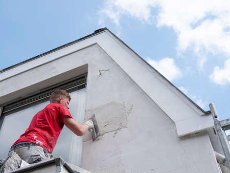Yesero en camisa roja trabaja sobre yeso blanco de la casa antigua durante los trabajos de aislamiento Foto de archivo