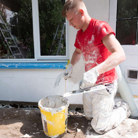 plasterer in red shirt works on white plaster of old house during insulation work Zdjęcie Seryjne