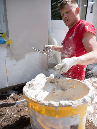 plasterer in red shirt works on white plaster of old house during insulation work Foto de archivo
