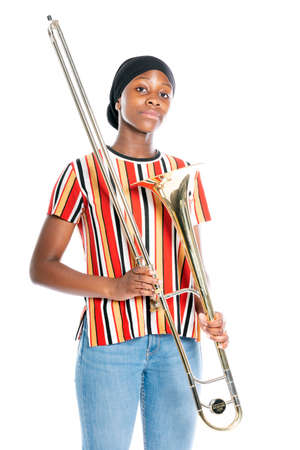 black teen girl with headscarf and musical instrument trombone against white background Imagens