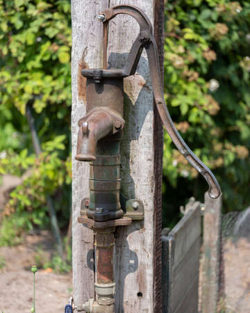 old and rusty cast iron water pump in vegetable garden Reklamní fotografie