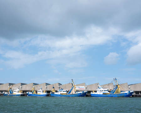 blue fishing boats lie in scheveningen harbor on stormy summer day in the netherlands