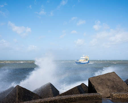 fishing boat at sea near harbor of scheveningen in holland in stormy weather and water spraying against pier Imagens
