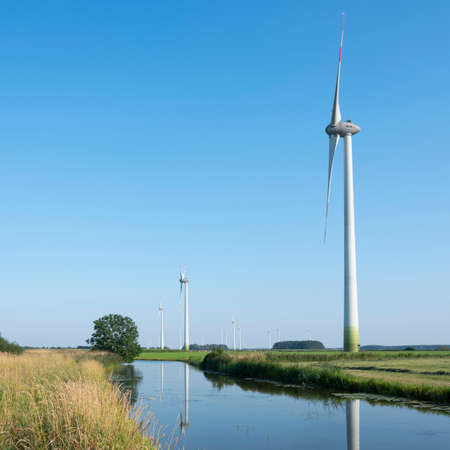 wind turbines in agriculture landscape of ostfriesland in the north of ostfriesland in lower saxony and blue sky