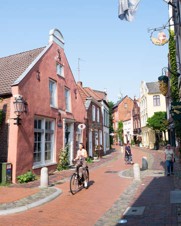 Leer, Germany, 26 august 2019: pedestrians and people on bicycle pass house of writer and poet wilhelmine siefkes in old german town of leer on sunny summer day