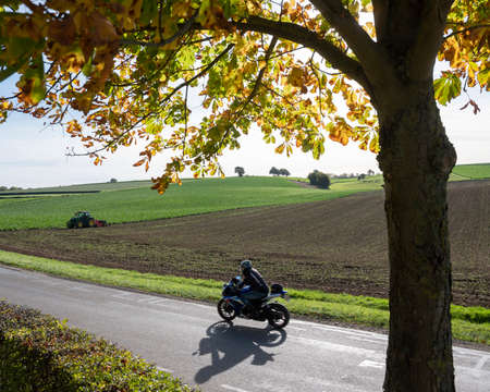 motorcycle on country road and tractor with harrow on field in dutch province of south limburg on sunny autumn day