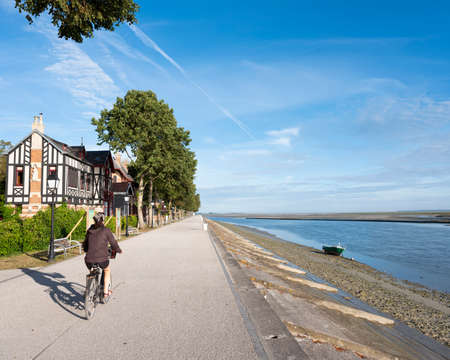 woman on bicycle in St-Valery-s-somme on sunny summer morning