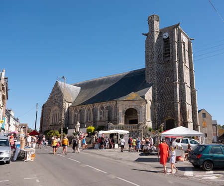people at market stalls near church of ault in french normandy Redakční