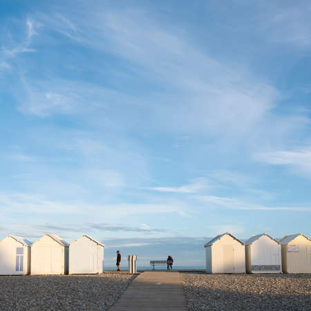 people near beach huts in cayeux s mer in french normandy under blue sky