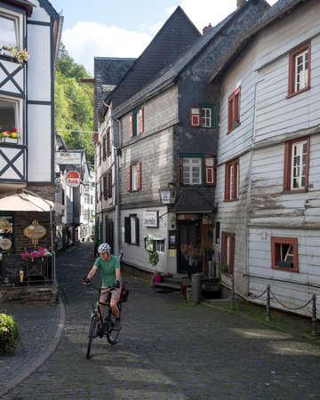 man on bicycle in old city of monschau in german eifel