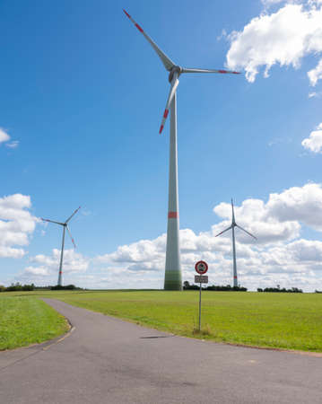 wind turbines in german eifel in green grass with blue sky and white clouds