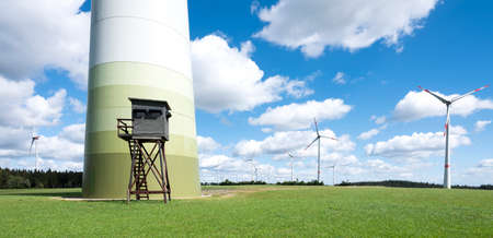 wind turbines and high seat in german eifel in green grass with blue sky and white clouds Reklamní fotografie
