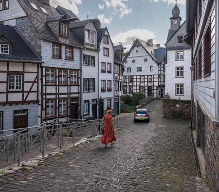 woman walks in old city of monschau in german eifel