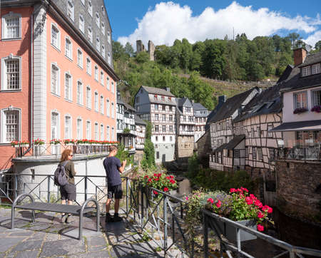 tourists take pictures in centre of old city monschau in german eifel