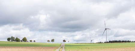 empty road between fields on high plane neer Cochem in german voreifel and wind turbines Reklamní fotografie