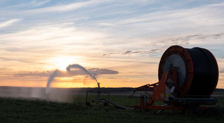 spraying of water in the french countryside of normandy at sunrise