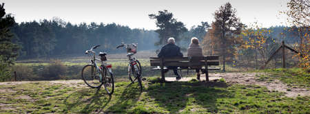 couple on bench resting from bicycle trip in autumn forest near Zeist in holland Reklamní fotografie