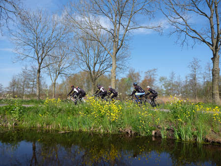 group of men on racing bikes on country road in the netherlands near woerden under blue sky in spring