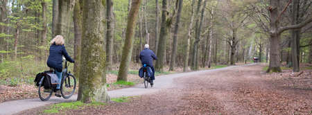 woman and man ride bicycle on early spring day in holland near utrecht