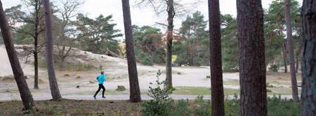 woman runs in forest near utrecht in the netherlands