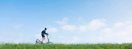 woman rides elliptigo bike on grassy dike in holland under blue sky