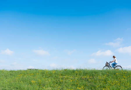 woman rides bicycle on grassy dike with flowers under blue sky