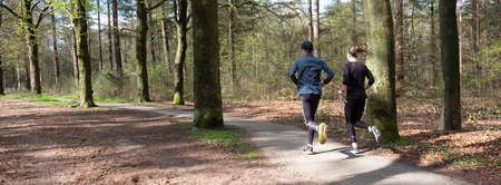 couple jogging in spring forest near utrecht in holland
