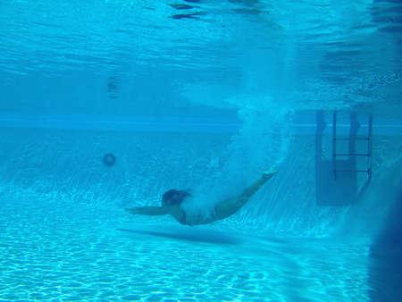 Een getalenteerde duiker neemt een duik in het zwembad Stockfoto