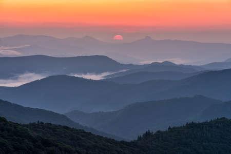 Sonnenaufgang zwischen Nord Carolinas iconic Hawksbill und Table Rock Berge, wie von der Blue Ridge Parkway gesehen