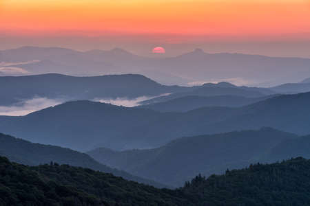 epic: Sunrise between North Carolinas iconic Hawksbill and Table Rock mountains as seen from the Blue Ridge Parkway Stock Photo