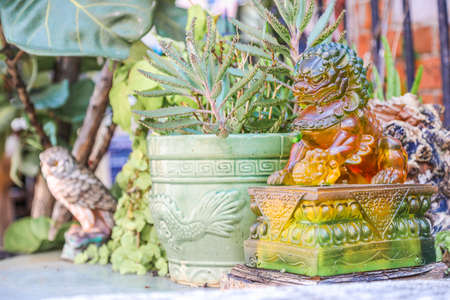 jade plant: Lion statue next to plants in backyard, Hong Kong