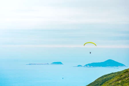 Paragliding above the ocean in Hong Kong Countryside