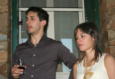 a young italian couple the man has a glass of wine to the hand
