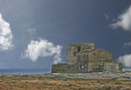 abandoned sinner house constructed to the foot of a Genoese tower in Sardinia