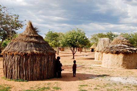pobreza: Pueblo Himba con cabañas tradicionales cerca de Parque Nacional de Etosha en Namibia, África