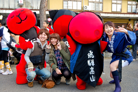 Young people celebrating a sake festival in the old town of Hida Takayama, Japan Редакционное