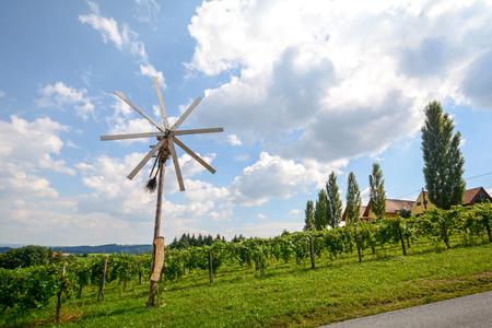 A road with a pinwheel Klapotetz through the vineyard, Southern Styria Austria Archivio Fotografico