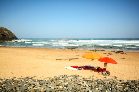 Beach umbrellas in the sand at beach Praia do Vale dos Homens near Aljezur, Algarve Portugal Standard-Bild