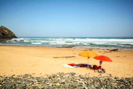 Strandparasols in het zand bij strand Praia do Vale dos Homens dichtbij Aljezur, Algarve Portugal
