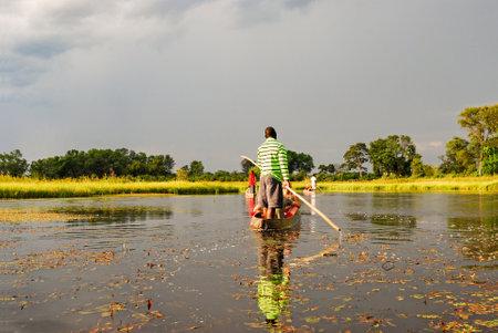 Canoe trip with traditional mokoro boat on the river through Okavango Delta near Maun, Botswana Africa