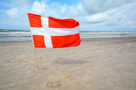 Danish flag in the wind at sand beach near Blavand, Jutland Denmark Stok Fotoğraf