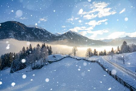 Snowy winter landscape in the Tyrolean Alps with icy road during snowfall, Austria Europe
