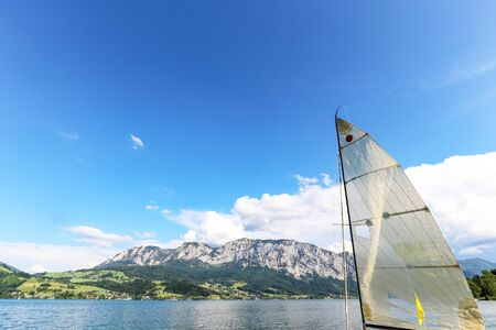 View to lake Attersee with sailing boat, Mountains of austrian alps near Salzburg, Austria Europe Stok Fotoğraf - 129320485