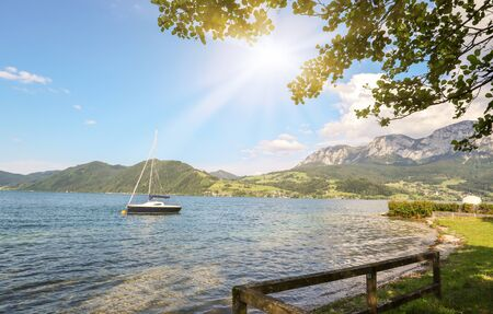 View to lake Attersee with sailing boat, Mountains of austrian alps near Salzburg, Austria Europe Stok Fotoğraf - 129320493